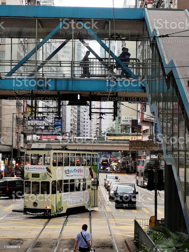 Double decker tram riding in Causeway Bay, Hong Kong island Historic double decker trams riding in Causeway Bay. People walking on a footbridge. Wan Chai district, Hong Kong island. Built Structure Stock Photo