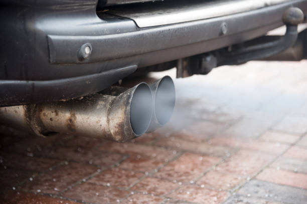 Double exhaust from an older car with diesel engine blows out gas with high particulate matter pollution, copy space Double exhaust from an older car with diesel engine blows out gas with high particulate matter pollution, copy space, selected focus diesel stock pictures, royalty-free photos & images