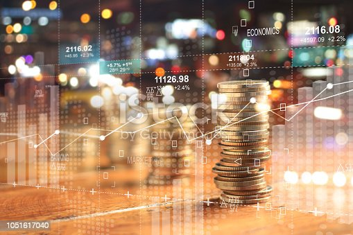 istock Double explosure with businesss charts of graph and rows of coins for finance at night city background. 1051617040