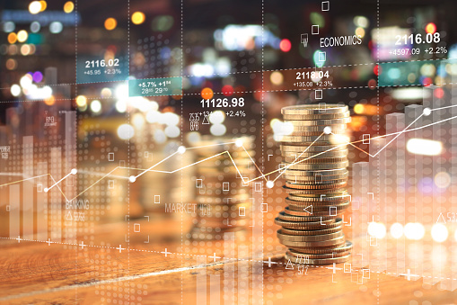 Double Explosure With Businesss Charts Of Graph And Rows Of Coins For Finance At Night City Background Stock Photo - Download Image Now