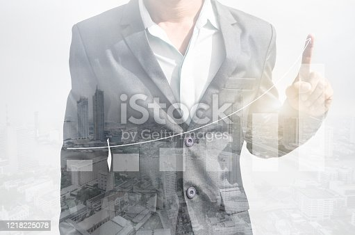 994786356 istock photo double exposure business man draw growth chart with cityscape background. concept for business working and leadership success with strategy plan management idea. 1218225078