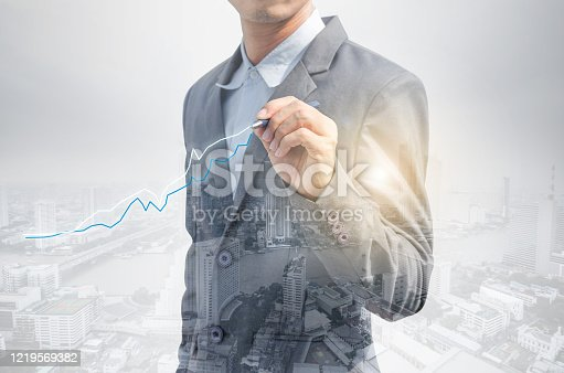 994786356 istock photo double exposure business man draw growth chart with cityscape background. concept for business working and leadership success with strategy plan management idea. 1219569382