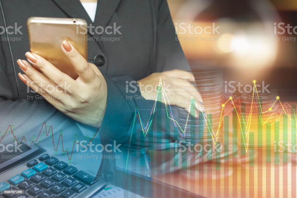 double exposure business woman hand holding smart phone,stack of coins,calculator,financial graph stock photo