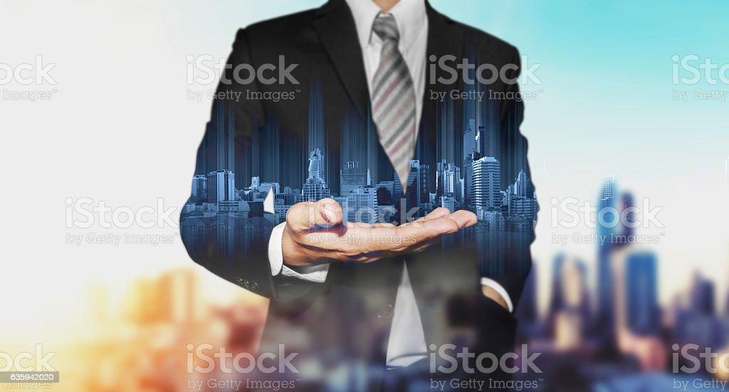 Double exposure businessman holding blue city hologram stock photo