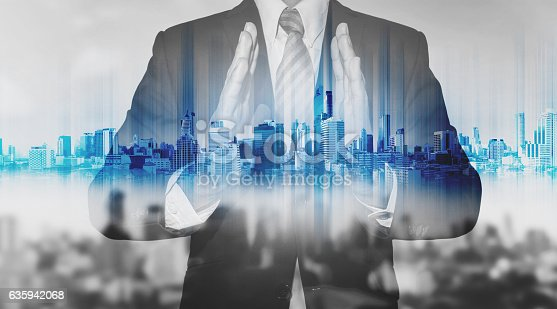 635942136istockphoto Double exposure businessman holding blue city hologram 635942068