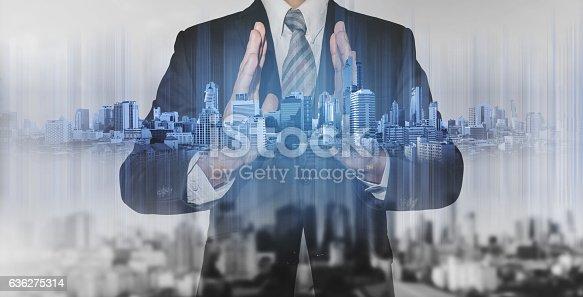 635942136istockphoto Double exposure businessman holding blue city hologram 636275314