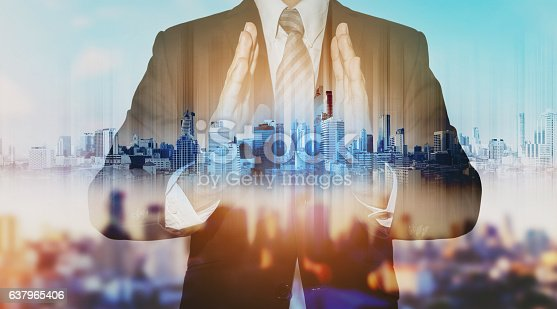 635942136istockphoto Double exposure businessman holding blue city hologram 637965406