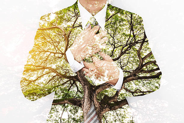 Double Exposure Businessman in Suit with Big Tree Double Exposure Businessman in Suit with Big Tree with Bright Sunlight tree hugging stock pictures, royalty-free photos & images