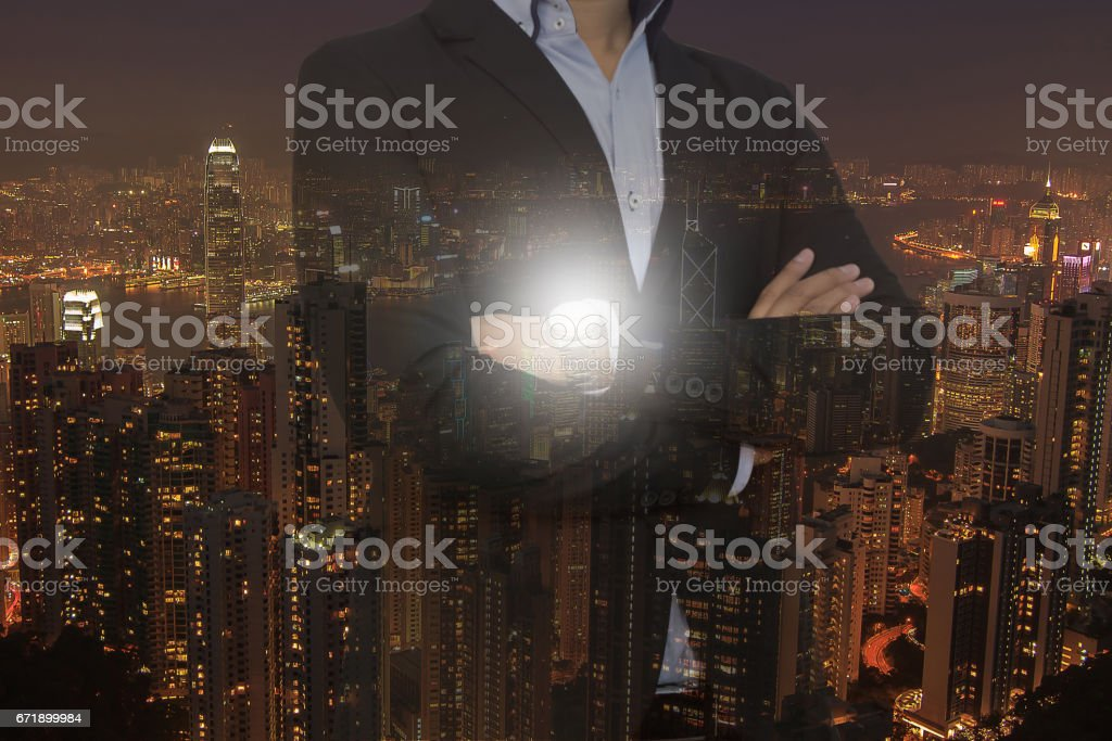 Double exposure businessman standing with his arms crossed against a city panorama. stock photo