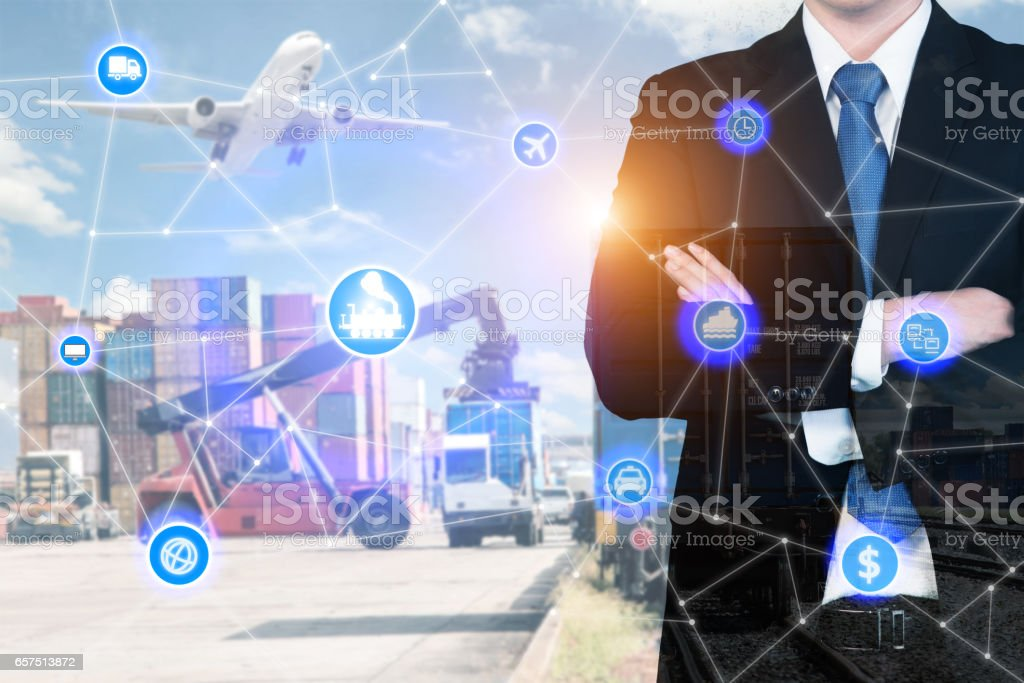 Double exposure businessman standing with his arms crossed with global business logistics system connection technology interface global partner connection stock photo