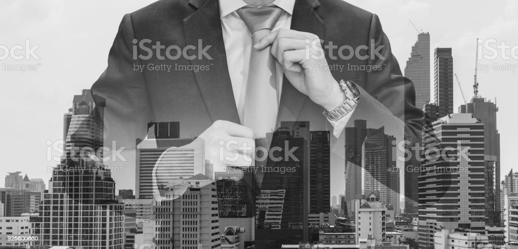 Double exposure businessman touching neck tie with modern buildings in Bangkok city background, Black and White stock photo