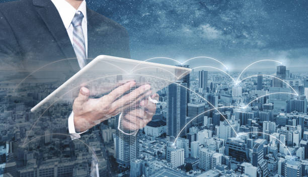 Double exposure businessman using digital tablet, and cityscape. Business network, blockchain technology and internet connection stock photo