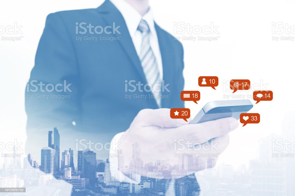 Double exposure, Businessman using mobile phone and notification icons stock photo
