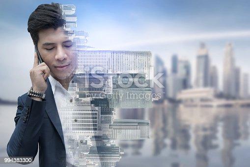 1054574018istockphoto Double exposure businessman using mobile phone. 994383300