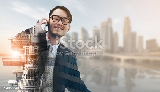 1054574018istockphoto Double exposure businessman using mobile phone. 994383340