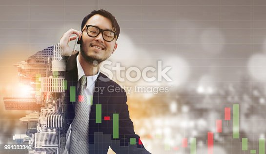 1054574018istockphoto Double exposure businessman using mobile phone. 994383346