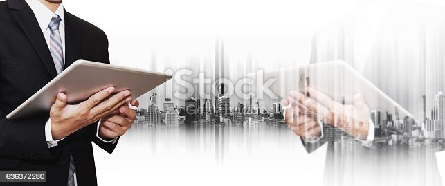 635942136istockphoto Double exposure businessman using smartphone and digital tablet with city 636372280