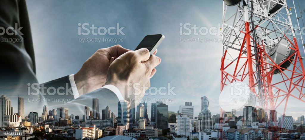 Double exposure businessman using smartphone with cityscape, and telecommunication towers stock photo