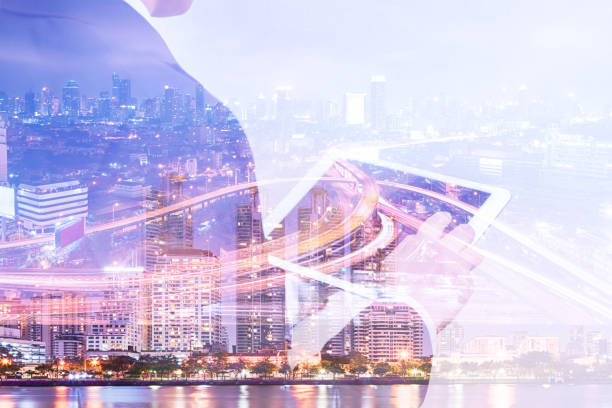Double exposure businessman using tablet and cityscape night view stock photo