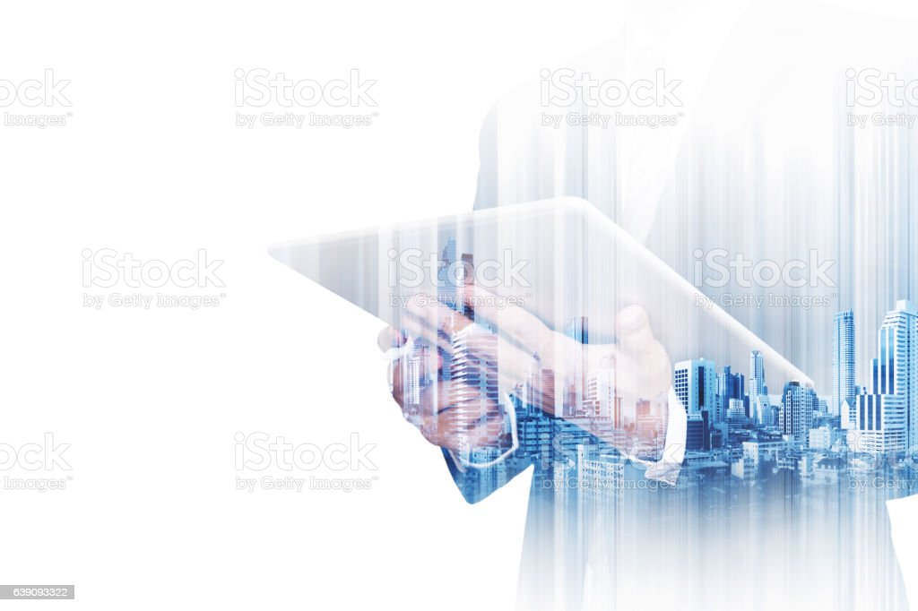 Double exposure businessman working on digital tablet with modern buildings stock photo
