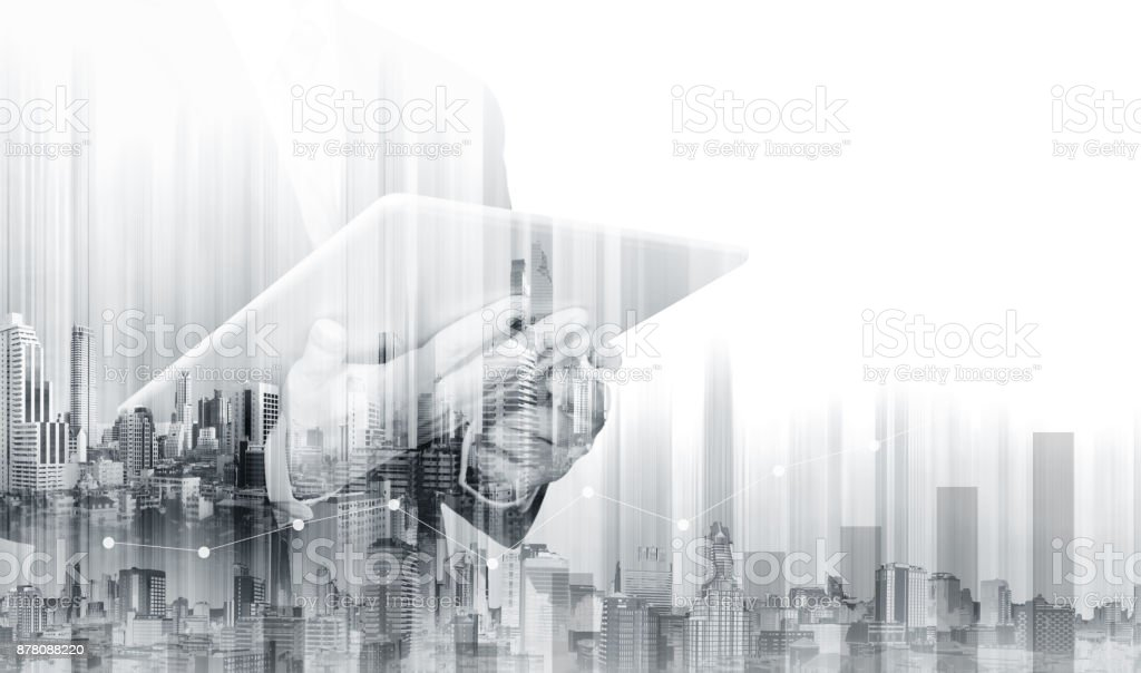 Double exposure Businessman working on digital tablet with modern buildings. Business growth and investment stock photo