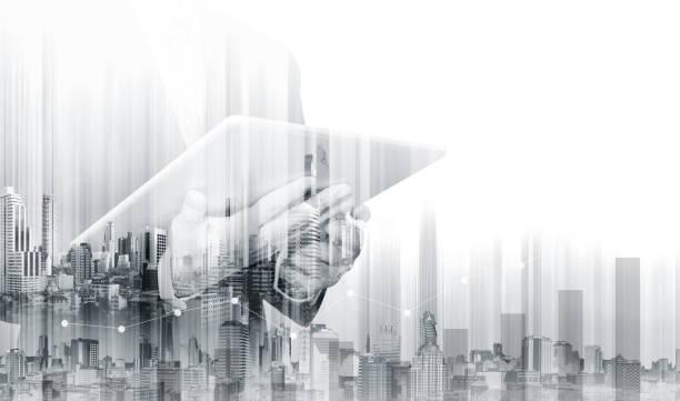 double exposure businessman working on digital tablet with modern buildings. business growth and investment - czarno biały zdjęcia i obrazy z banku zdjęć