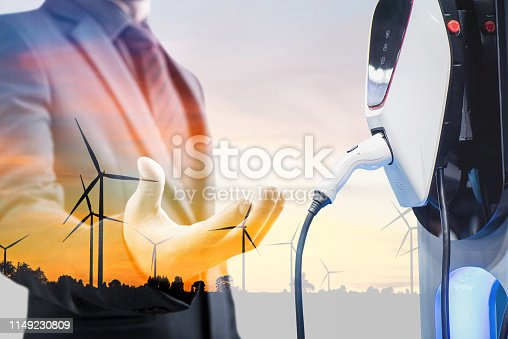 istock double exposure businessmen and silhouette of wind turbine at sunset with electric car battery charger station. Green energy for new innovative technology EV Electrical vehicle concept. 1149230809
