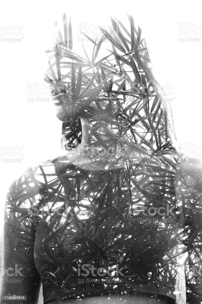 Double exposure close up of a young natural beauty with closed eyes combined with a healthy tree whose branches blend seamlessly into her healthy being, black and white stock photo
