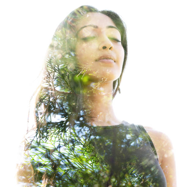 Double exposure close up of a young natural beauty with closed eyes combined with a healthy tree whose branches blend seamlessly into her healthy being stock photo