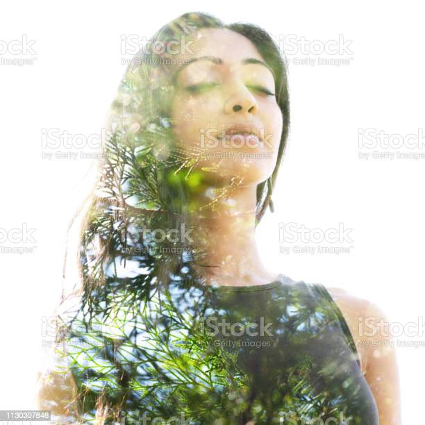 Photo of Double exposure close up of a young natural beauty with closed eyes combined with a healthy tree whose branches blend seamlessly into her healthy being