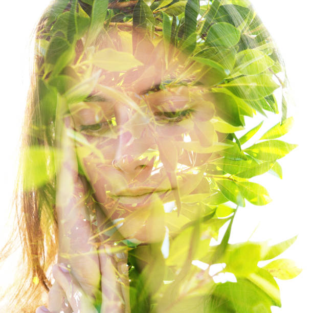Double exposure close up portrait of a naturally beautiful fair-skinned woman and bright green tropical leaves stock photo