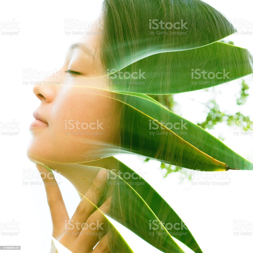 Double exposure close up profile portrait of a young natural beauty with closed eyes, relaxing and softly touching her throat and chin as her face and hair combine perfectly with bright tropical leaves stock photo
