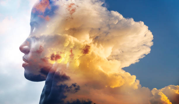 Double exposure, close-up of an African American girl and layers of stunning fluffy clouds stock photo