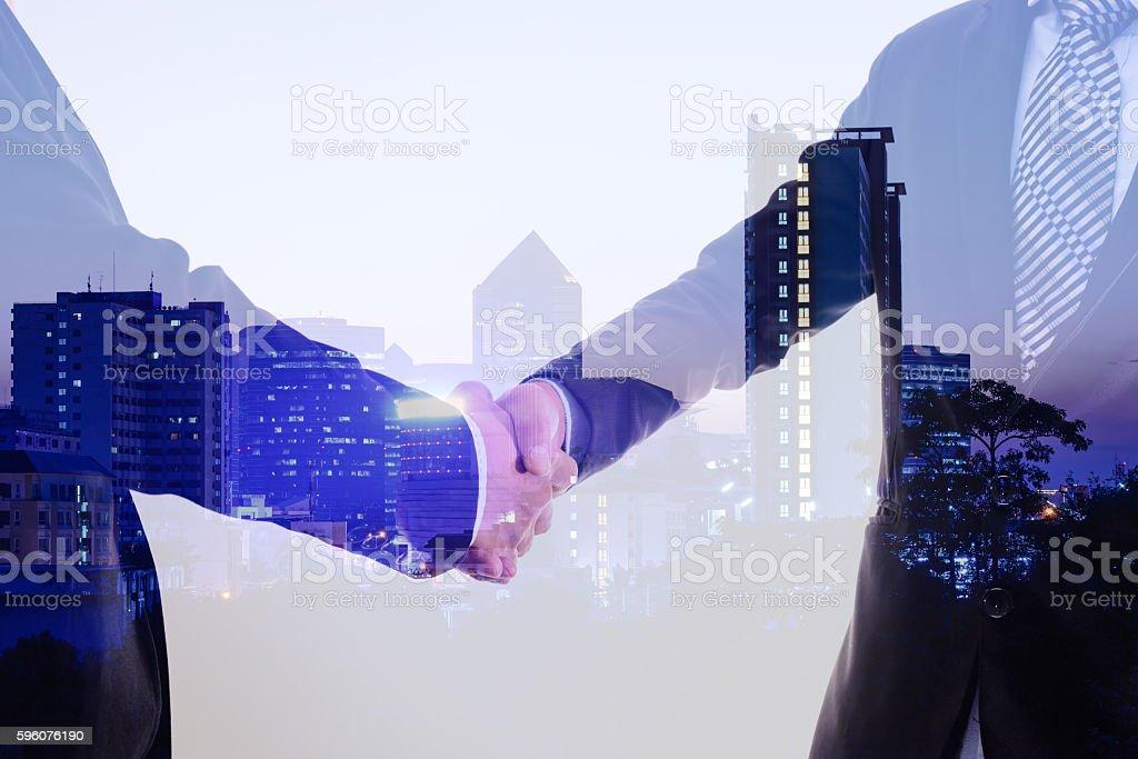 Double exposure closeup of businessman handshake on city background. royalty-free stock photo