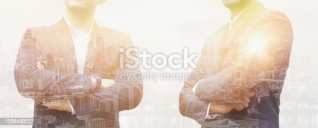 994786356 istock photo Double exposure effect-two young businessman standing and thinking outdoor,with sunlight and cityscape,with white background,concept business,finance and investment,banner header panoramic horizontal 1209430227