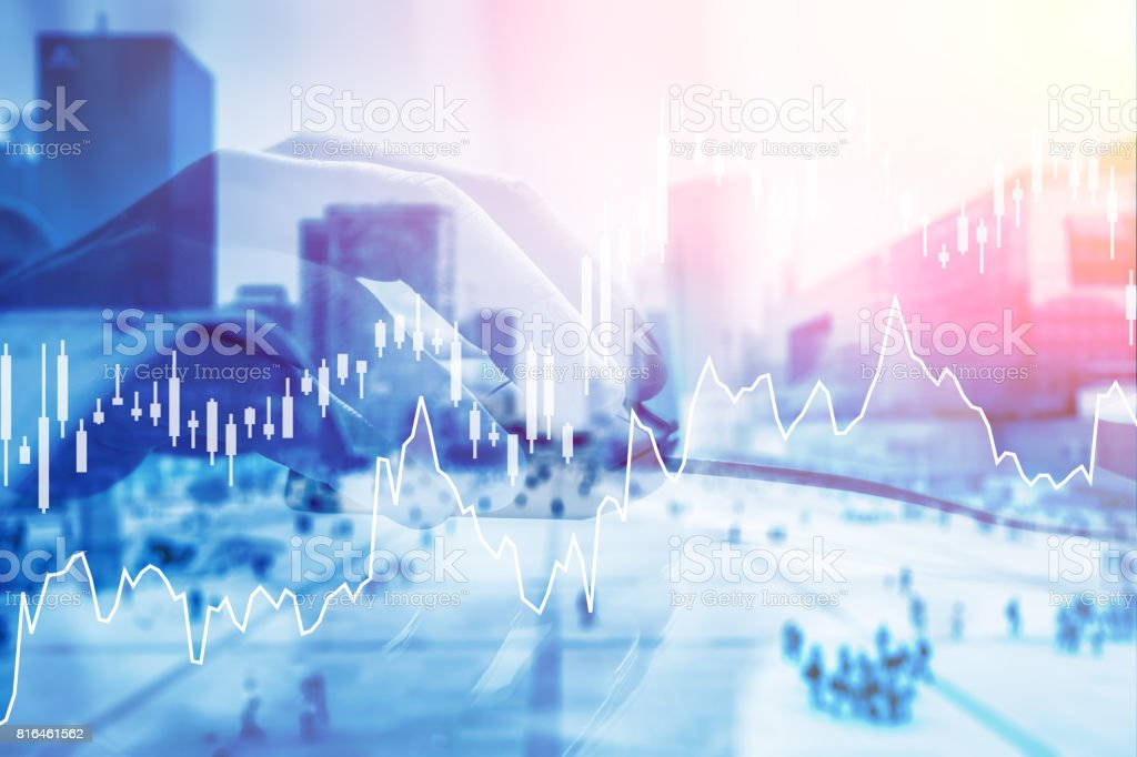 Double exposure hand holding computer mouse, financial charts, business district stock photo
