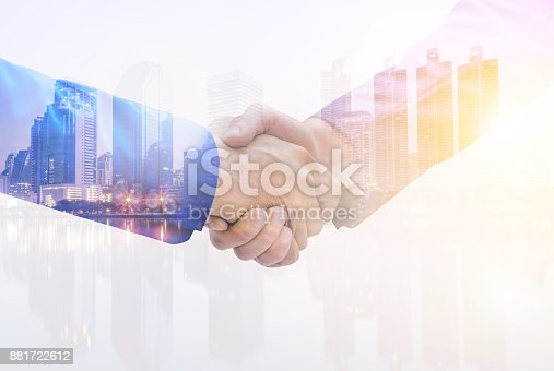 istock Double Exposure image of a businessman handshake on city nightlife background. The concept of business partnership. 881722612