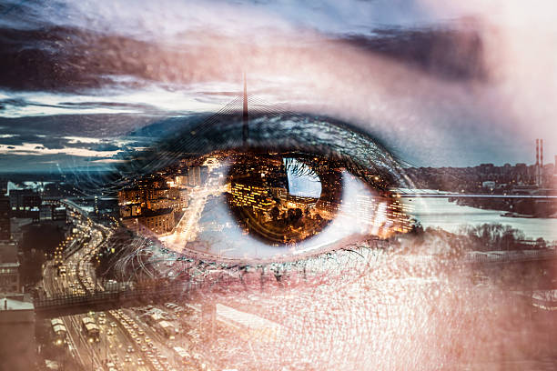 Double exposure image of an eye with city stock photo