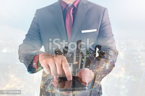 1054574018istockphoto Double exposure image of businessman standing and touching his smart phone overlay with cityscape image 1071002494