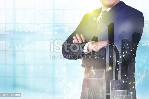 1079450712 istock photo Double exposure image of businessman standing with crossed arms overlay with cityscape image 1071002384