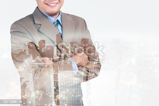 1079450712 istock photo Double exposure image of businessman standing with crossed arms overlay with cityscape image 1071006116