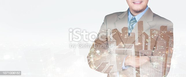 1079450712 istock photo Double exposure image of businessman standing with crossed arms overlay with cityscape image 1071006152