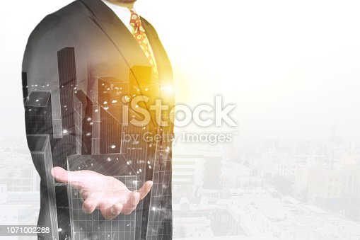 1079450712 istock photo Double exposure image of businessman standing with open hand overlay with cityscape image 1071002288