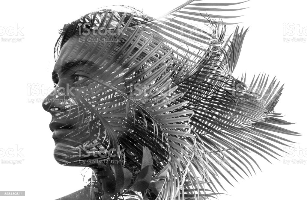 Double exposure in black and white of a young sexy man with a blended with branches of a tropical tree showing the perfect beauty of nature's creation stock photo
