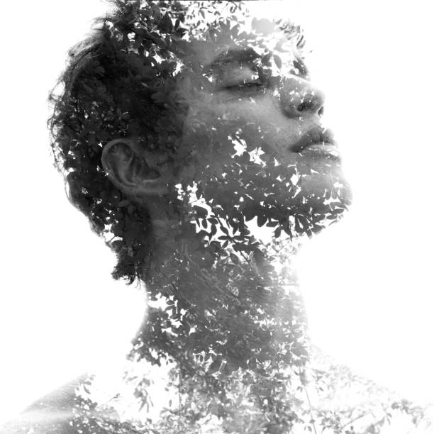 Double exposure in black and white of a young sexy man's portrait blended with branches of a tropical tree, showing the perfect beauty of nature's creation stock photo