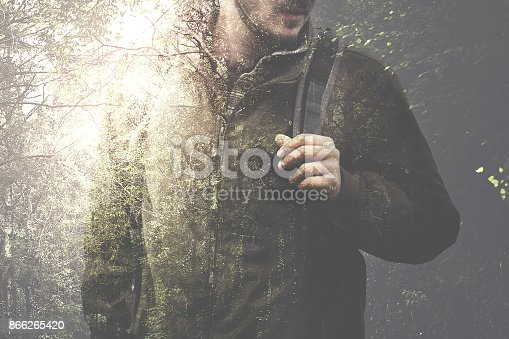 istock double exposure man walking in the forest 866265420