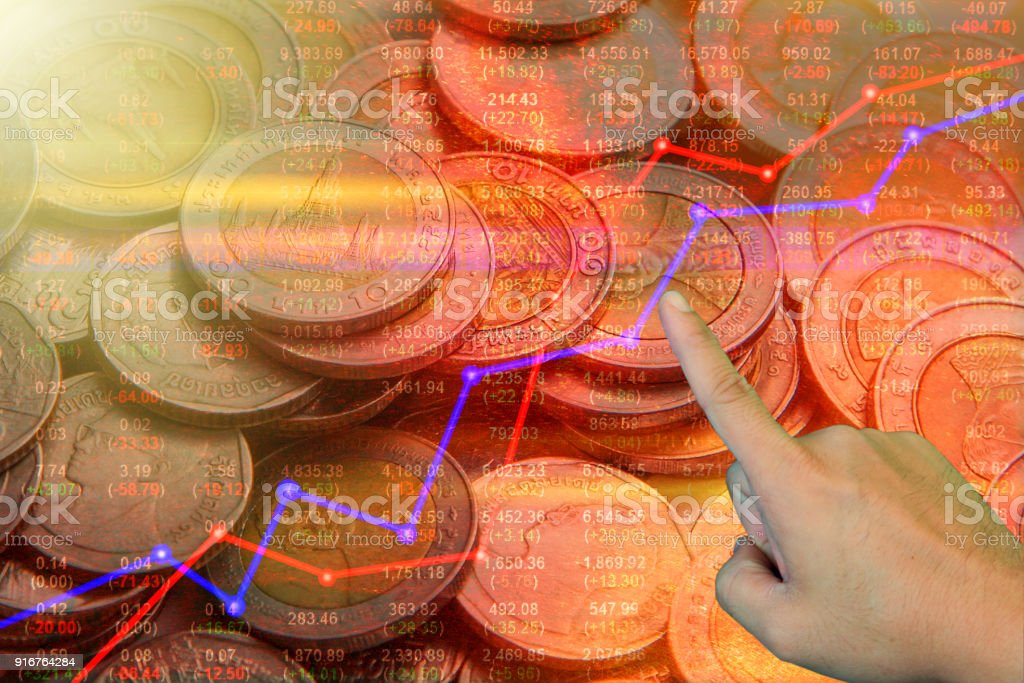 Double exposure money coins on trading graph and stock market board background stock photo