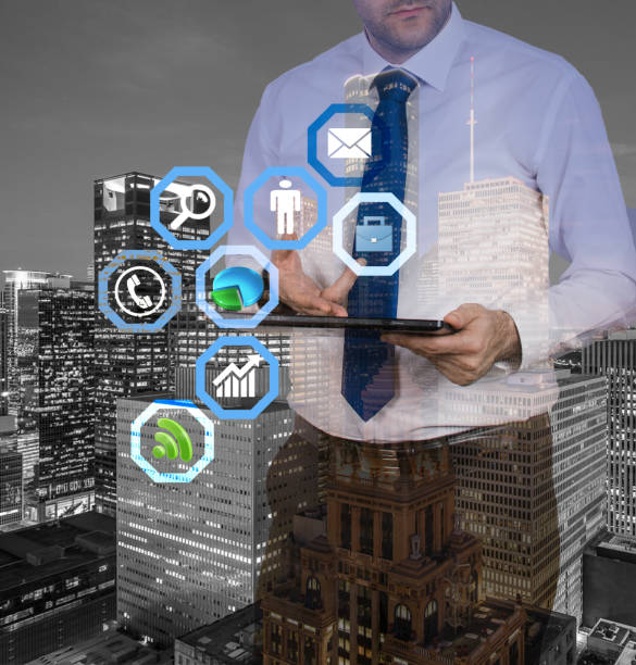 Double exposure of a businessman with his tablet and city at night stock photo