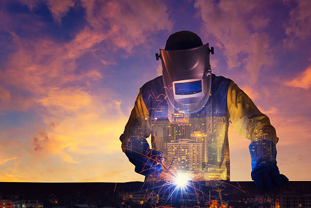 Double exposure of a downtown city and Industrial Worker Double exposure of a downtown city and Industrial Worker welding steel structure with sunset sky in background for industrial and construction concept metal industry stock pictures, royalty-free photos & images