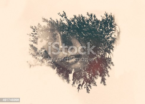 Subtle image of foliage surrounding a woman's mouth in a graphic double exposure photographic effect